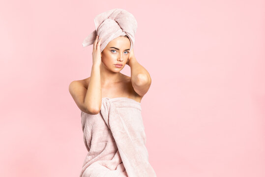 Beautiful young bare shouldered female wrapped in towels while enjoying healthy smooth skin after spa procedure on pink background