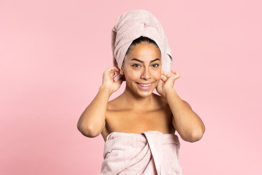 Happy young ethnic bare shouldered female with bath towel on head and perfect olive skin looking at camera against pink background while representing beauty and skincare concept