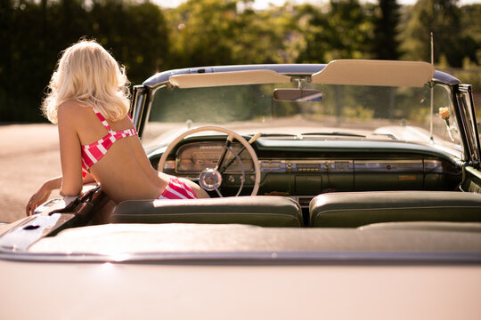 Back view of anonymous woman in striped swimwear peeking out from retro vehicle on sunny summer day in countryside