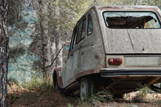 Abandoned old fashioned automobile with broken window and rusty metal details parked in forest