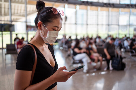 Side view of ethnic female in protective mask standing in departure lounge of contemporary airport and surfing Internet on cellphone