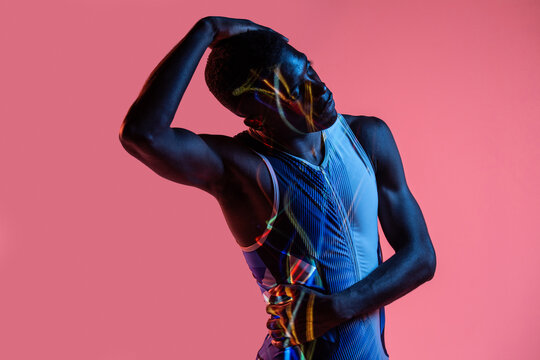 Professional young African American sportsman in active wear performing stretching exercise during training in studio with colorful background and neon lights with eyes closed