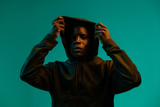 Serious young African American male in black hoodie covering head with hood against green background in studio