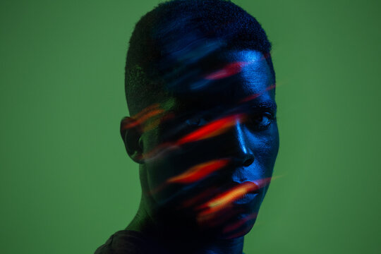 Serious confident young African American male with colorful neon lights on face looking at camera against green background