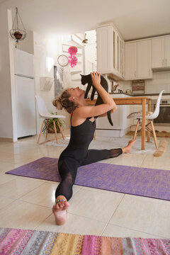 Vertical photo of a woman with a black cat in her hands smiling while doing yoga in a mattress at home