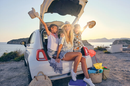 Mother with her two children in straw hats and summer clothes sitting in the trunk of a car with their arms raised in happy gestures with the sea on the background during sunrise