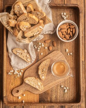 Top view composition with typical Catalan biscuits carquinyolis with roasted almonds served on wooden tray