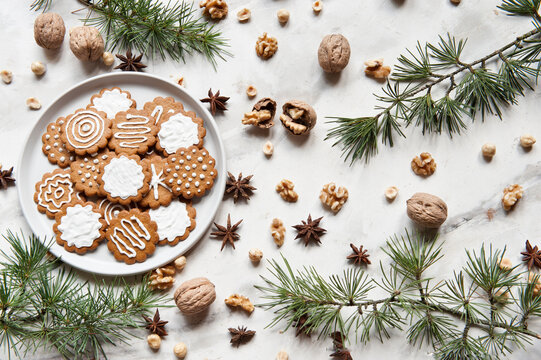 Top view composition with sweet homemade Christmas cookies decorated with white sugar icing served on plate placed on white table near various nuts and fir branch