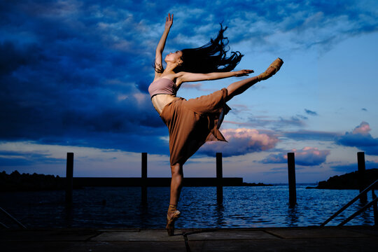 Side view of graceful ballerina in pointe shoes dancing on pier near lake while balancing on leg on background of amazing sunset in evening