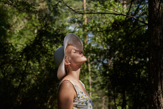 Side view of tranquil female standing in woods in summer and enjoying fresh air with closed eyes