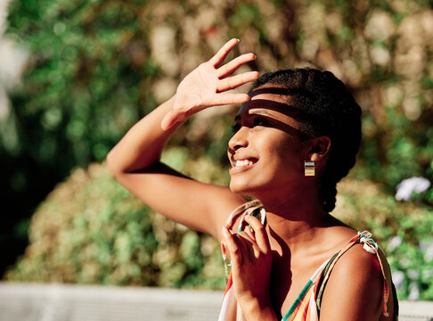 Side view of cheerful young African American female covering eyes from sunlight while spending summer day in green park