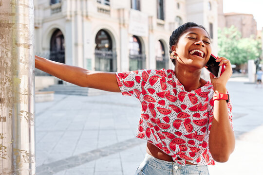 Cheerful young African American female in casual colorful shirt laughing happily during phone conversation while standing on city square against old building