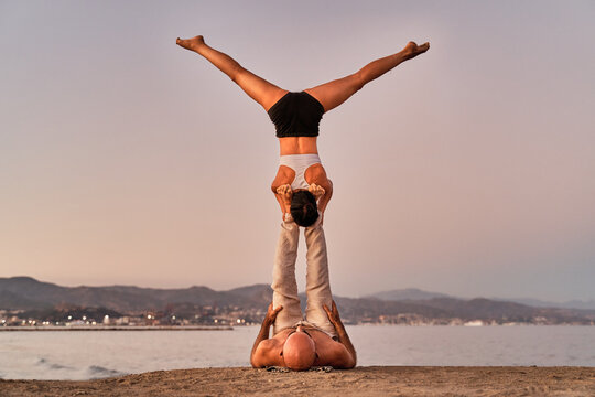 Slender woman balancing in Handstand on feet of strong man while doing acroyoga together on seashore in evening