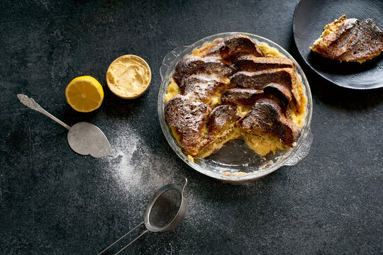 Top view of traditional bread pudding with custard, served with aromatic orange zest butter and powdered sugar on dark background