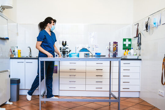 Full body woman in medical mask and uniform walking near table in modern office of vet clinic