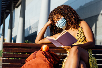 Thoughtful African American female in medical mask sitting on bench in city and enjoying interesting story while resting during coronavirus outbreak