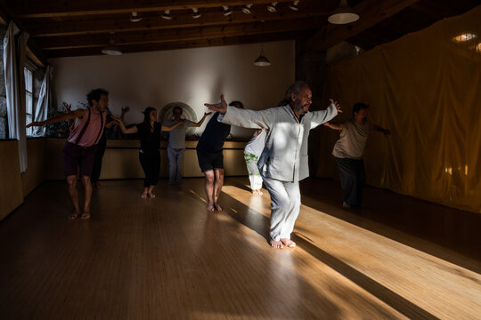 Group of people with instructor performing flowing movements with outstretched arms during chi kung practice in studio