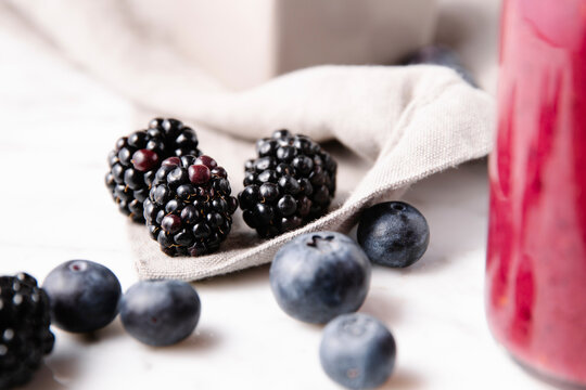Close up detailed shot of blackberries beside blueberries and a gray linen cloth over a marble surface.