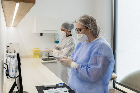 Female medical workers with protective face masks while preparing for medical procedure in hospital