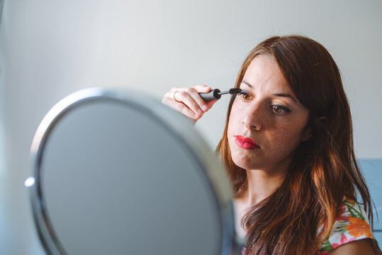 Young long haired freckled female in casual wear looking at mirror and applying mascara during makeup session at home