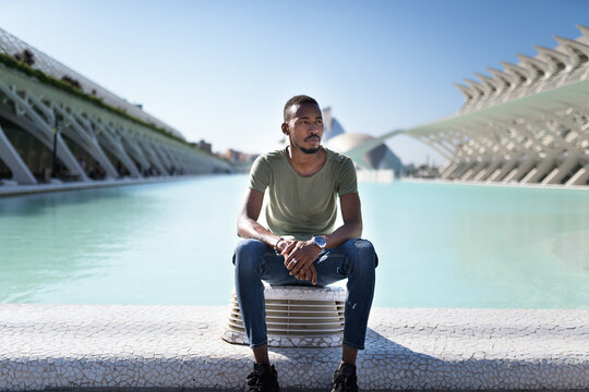 Portrait of thoughtful man sitting in front of water fountain in city