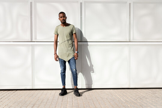 Serene African American male in stylish clothes standing with closed eyes near modern building and enjoying sunny weather