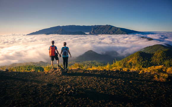 Back view of tender traveling couple standing on hill holding hands while admiring spectacular scenery on clouds over mountainous terrain