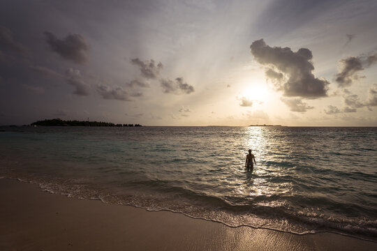 Silhouette of distant unrecognizable traveler standing in waving sea water during sunset while spending summer holidays in Maldives islands