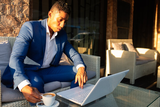 Young African American male entrepreneur in formal wear working on laptop and thinking about financial problem while sitting in lounge zone of modern cafeteria
