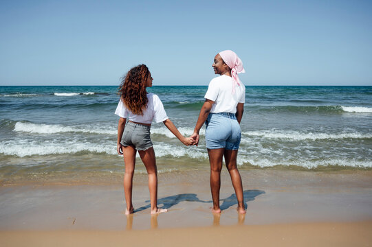 Rear view of smiling mother and daughter enjoying beach