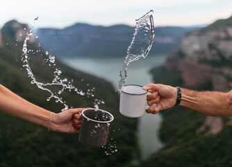 Anonymous couple of tourists standing on hill with cups of splashing water on background of river and highlands