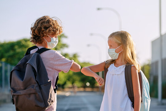 Two kids with school bags and masks greeting each other with a gesture of touching elbows in the street in front of a park