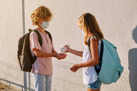 Blonde girl with blue school bag and mask throwing disinfectant gel on the hands of a blonde boy wearing a mask in the street
