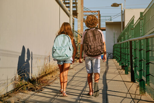 Two children with black school bags on their backs walking down an industrial passage going to school in the morning