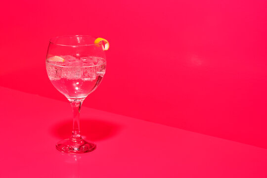 Transparent glass of tasty gin tonic cocktail with ice with lemon twist peel on table in pink background