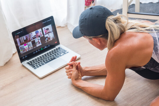 From above back view of fit female athlete in sportswear watching video online on laptop before home workout