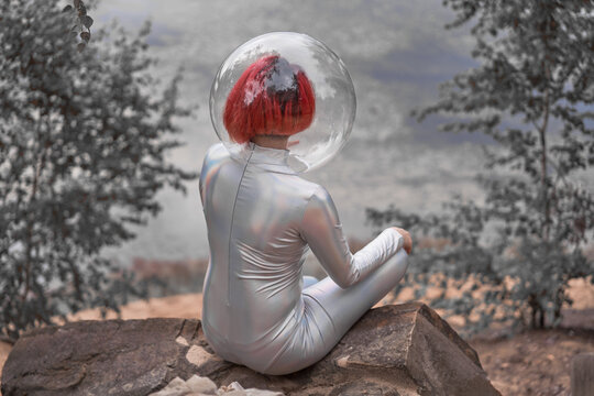 Back view of unrecognizable futuristic young red haired female in silver space suit and glass helmet sitting near flooding river