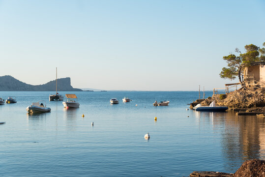 Picturesque scenery of old cove near sea with moored boats on rocky shore and trees under blue sky in Sa Caleta