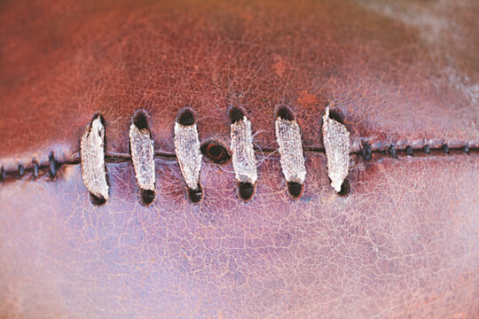 close up of AFL football - leather stitching