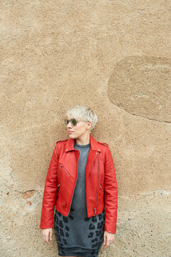 Stylish short-haired blonde in red jacket and dress in the street