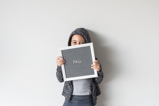 A Girl Hiding Her Face With A Letterboard Sign