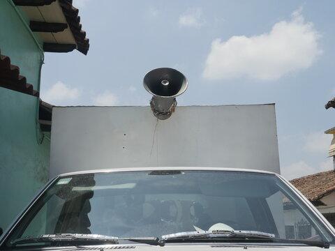 Old loudspeaker on top of car