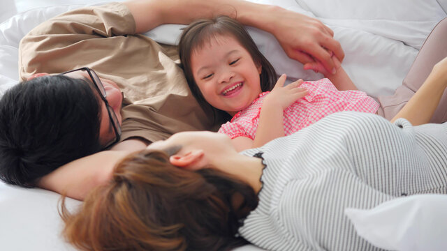Happy family with mother, father and disabled daughter spending time together in bedroom..