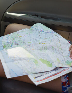 Western United States road map sits on woman's lap