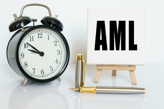 On the table there is a clock, a pen and a stand with a card on which the text is written AML. ANTI-MONEY LAUNDERING ANTI MONEY LAUNDERING