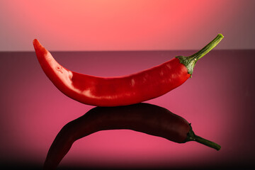 red hot long chili pepper on a red dark background