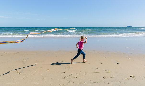 Child Running on Beach with Wand