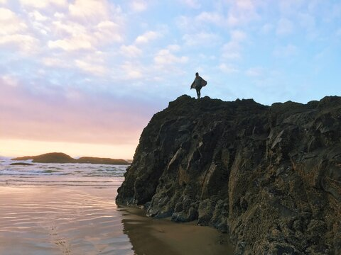 Young Woman Spreading Arms Like Wings On Top Of Rocky Outcrop Along Ocean Shore
