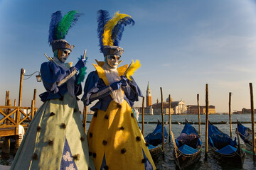 The Carnival of Venice: Molo San Marco, Venice, Italy. Masked revellers pose in front of the Basin of St Mark, with gondolas and the Chiesa di San Giorgio Maggiore in the background