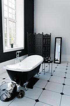 Bathroom interior with windows and bathtub with legs